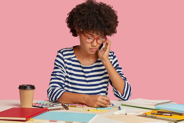 Photo of serious busy female worker with afro hairstyle, creats illustration for project work, talks with partner via cellular, wears transparent glasses and striped clothes, isolated over pink wall