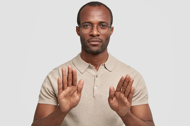 Photo of serious calm african american guy shows stop gesture