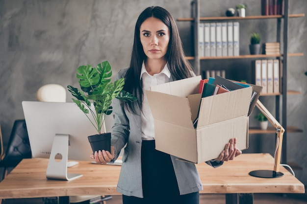 Photo of serious chief manager lawyer girl have company crisis bankrupt hold belongings cardboard box with flower plant quit occupation wear blazer jacket suit in workstation workplace