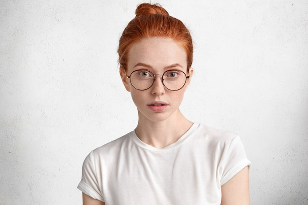 Photo of serious clever redhead female student with ginger hair knot, wears round spectacles, comes on lecture at university, isolated over white
