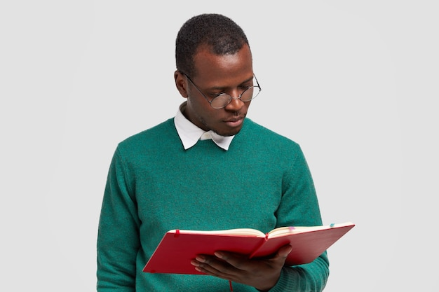 Photo of serious concentrated dark skinned young man focused in textbook, wears round spectacles, green sweater, studies at college