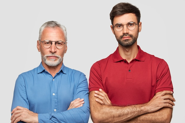 Photo of serious confident male colleagues keep arms folded, thinks about new project, belong to different age group, have common interests in business sphere, isolated over white wall