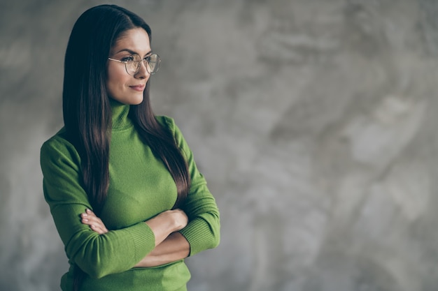 Photo of serious confident woman looking into empty space with arms crossed dreaming about successful future isolated grey wall concrete color background