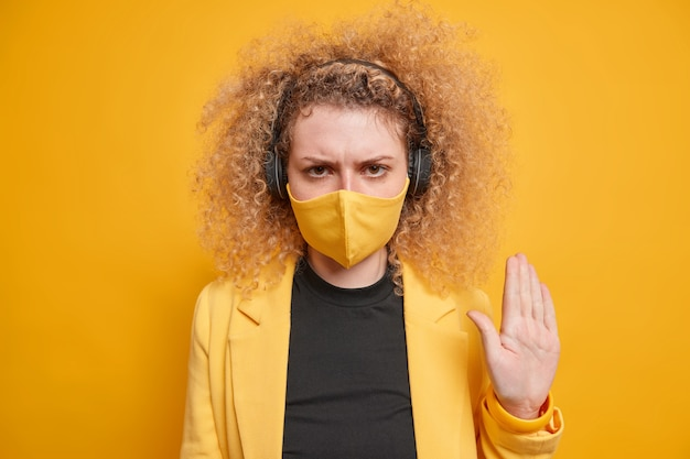 Photo of serious curly haired woman makes stop hand gesture to protect from covid 19 asks to stop coronavirus outbreak and keeps social distancing listens music via headphones looks very strict