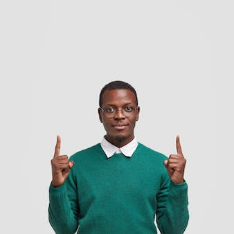 Photo of serious dark skinned man with confident facial expression, indicates with both index fingers upside, wears spectacles and green jumper