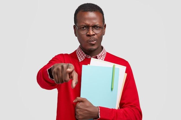 Photo of serious dark skinned man with sullen expression, indicates with index finger directly , has displeased look, dressed in red jumper