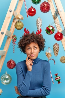 Photo of serious dark skinned woman with curly hair thinks what present to buy for husband on new year dressed in casual turtleneck and reindeer horns surrounded by shiny baubles hanging on ladder