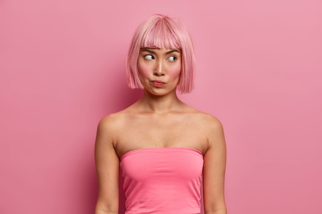 Foto di una donna gravemente scontenta con l'acconciatura a caschetto, vestita con un top rosa, guarda pensierosa, pensa seriamente all'offerta, trova il modo di risolvere la situazione problematica, medita sulla decisione