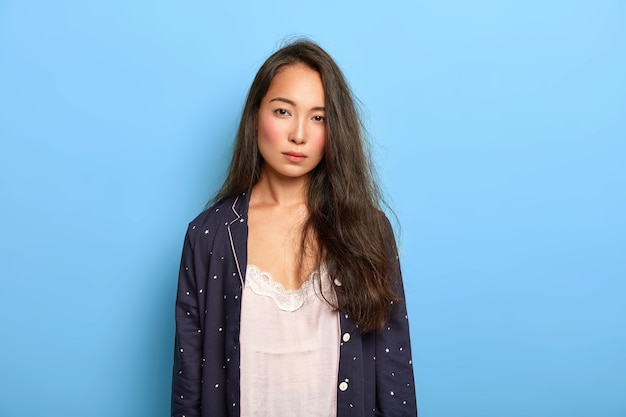 Photo of serious dissatisfied brunette asian woman looks with tiredness at camera, has not enough sleep, wears nighclothes
