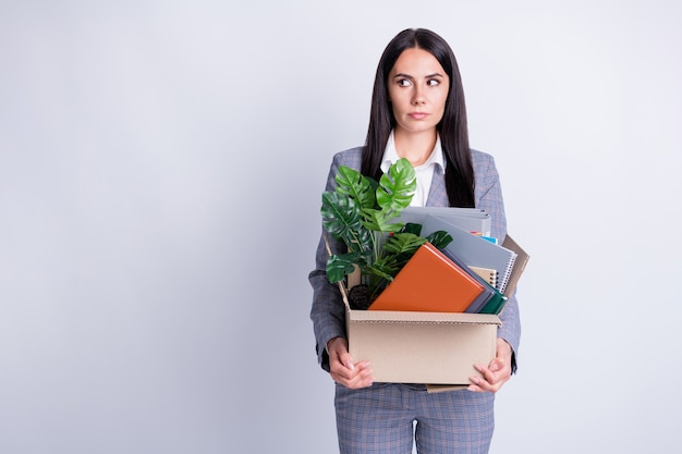 Photo of serious fear worker dismissed lady world financial crisis lost work hold carton box stuff fired quit look side empty space scared angry boss formalwear isolated grey color background