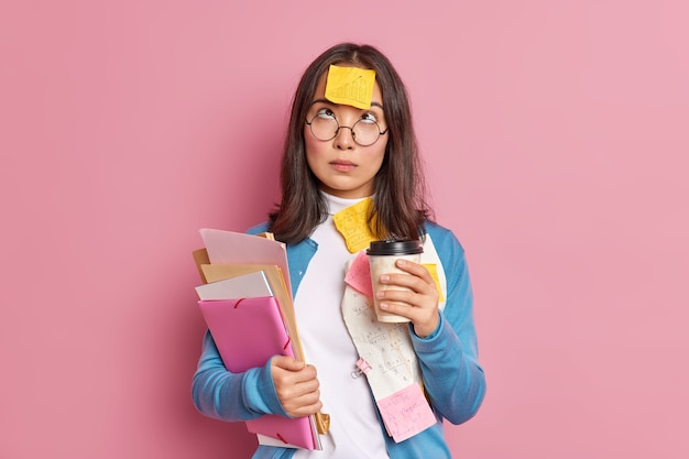Photo of serious female student has coffee break concentrated above has reminding sticker stuck on forehead