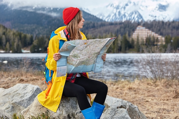 Photo of serious female traveler with backpack explores new destination, reads map while sits on stone, looks for some place