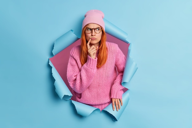 Photo of serious gloomy woman with red hair looks pensively aside wears pink hat knitted sweater.