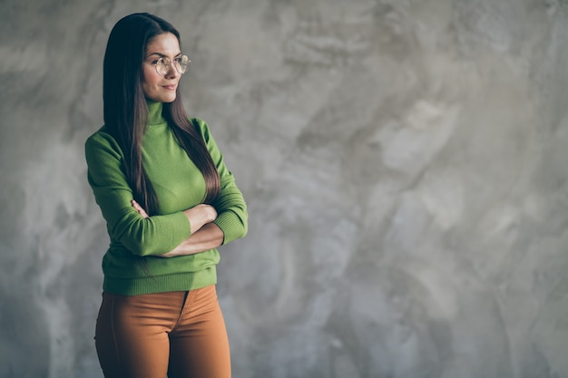 Photo of serious interescted confident woman looking into empty space in green turtleneck orange pants with arms crossed isolated in spectacles on grey wall concrete background
