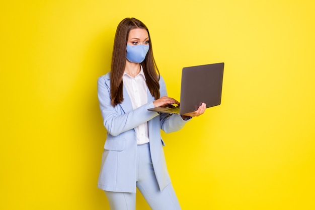 사진 진지한 변호사 보스 레이디는 원격 코비드 검역소에서 노트북 채팅 칼라 파트너를 사용하여 파란색 재킷 블레이저 바지 바지 의료 마스크 격리된 밝은 광택 색상 배경을 착용합니다.