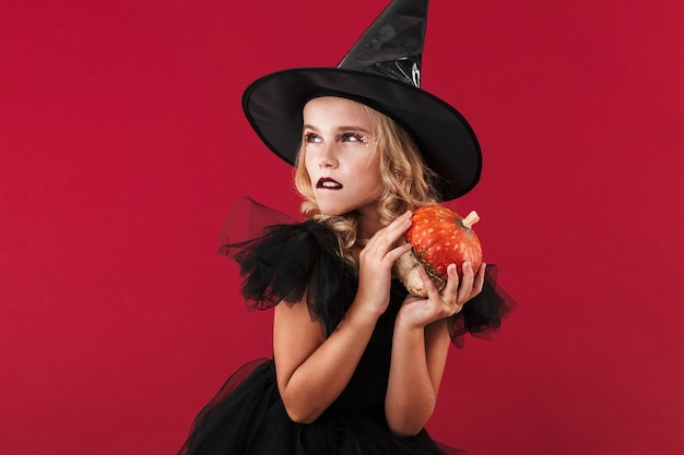 Photo of serious little girl witch in carnival halloween costume