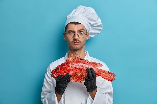 Photo of serious male cook carries fish looks directly at camera asks chef for advice what better to prepare tries tasty yummy recipe