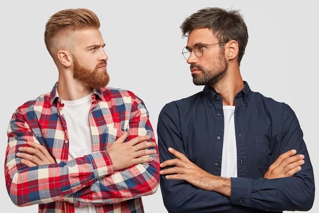 Foto di avversari maschi seri stanno con le mani incrociate, si guardano l'un l'altro, hanno competizione, stanno spalla a spalla