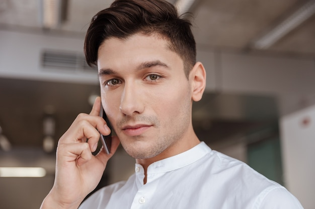 Photo of serious man dressed in white shirt talking by the phone indoors. coworking. looking at camera.
