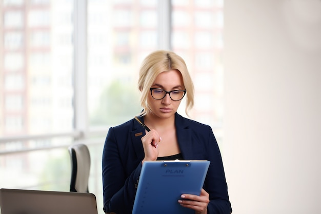 Photo of serious manager or director woman wearing formal clothing and eyeglasses holding in hands paper documents while working in office on laptop