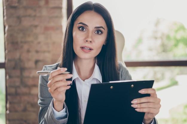 Photo of serious smart expert boss girl have online webcamera job interview listen applicant write clipboard information wear blazer jacket suit in workplace workstation