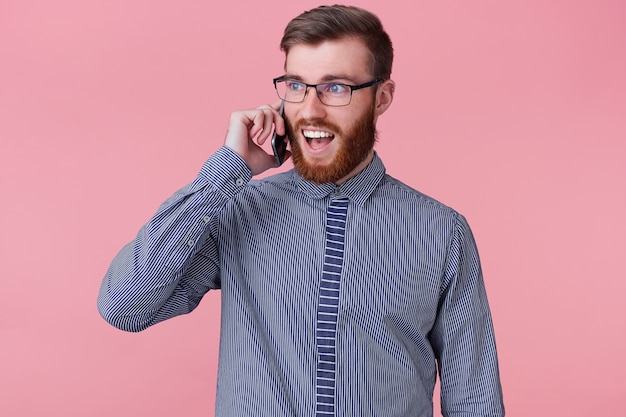 Photo of serious smiling happy successful bearded man with glasses calling with his phone, smiles broadly, happy amazed, isolated on a pink background.