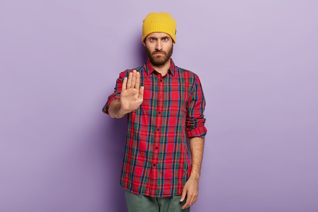 La foto dell'uomo serio con la barba lunga severa mostra il gesto di arresto, vestito con abiti alla moda, rifiuta qualcosa, chiede di non compiere azioni proibite
