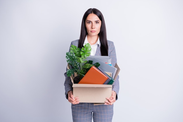 Photo of serious stressed unhappy worker young dismissed lady hate world financial crisis lost work hold carton box stuff fired quit search new job formalwear isolated grey color background