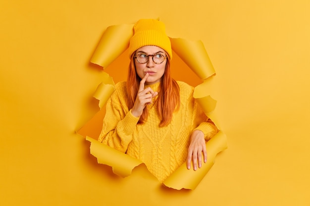Photo of serious thoughtful woman with red hair keeps finger near lips looks pensively away recalls something or considers future plans wears hat jumper breaks through yellow paper hole. let me think.