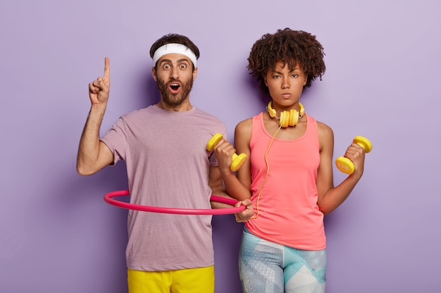 Photo of serious woman holds yellow dumbbells, wears pink top and leggings, surprised unshaven man points above on blank space, uses hula hoop for staying fit, isolated on purple wall