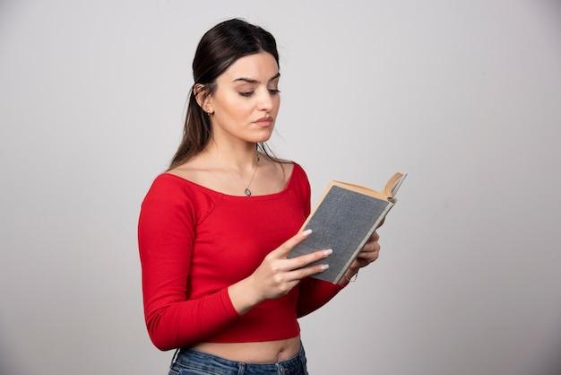 Foto di una donna seria che legge un libro e tiene una matita.