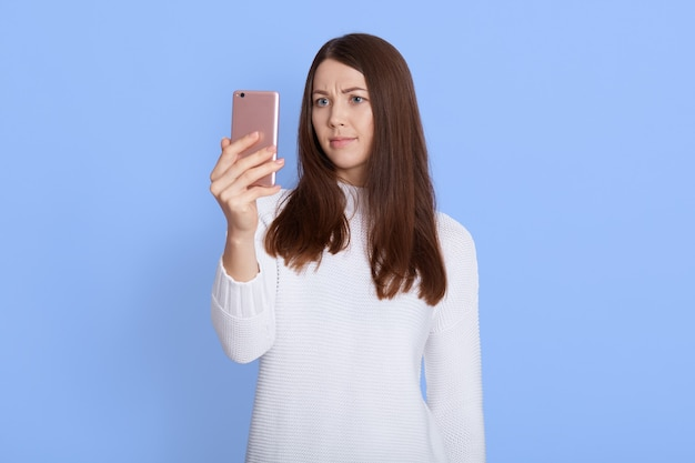 Photo of serious woman uses modern device, browses in social media, wears casual clothes, isolated on blue wall