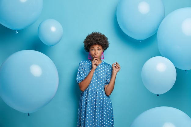 Photo of serious woman with curly hair, dressed in fashionable clothes, enjoys party, poses against blue wall, has pleasant conversation. pretty lady celebrates birthday, has awesome day