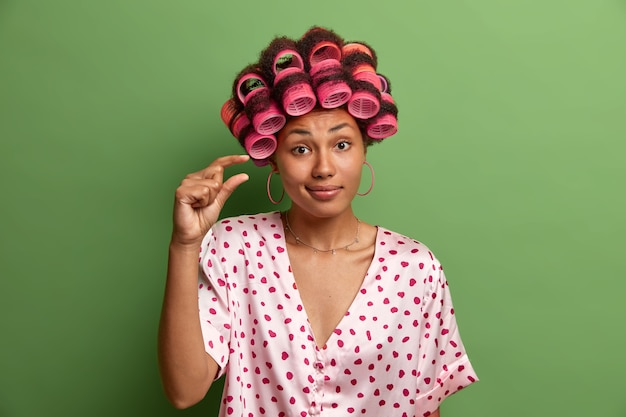 Photo of serious woman with dark skin, shapes very little object, shows tiny gesture, small size of something, says she needs not much time to get ready for date or meeting, makes hairdo with curlers
