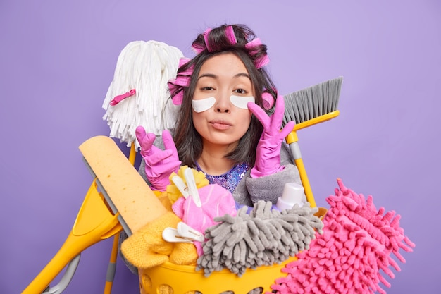 Photo of serious young asian woman applies patches under eyes has scrupulous look cares about cleanliness and purity busy doing housework isolated over purple wall