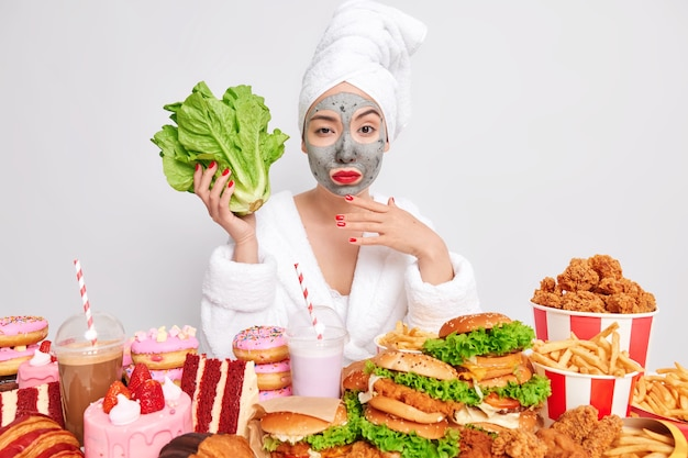 Photo of serious young asian woman  holds lettuce leaves surrounded by fast food