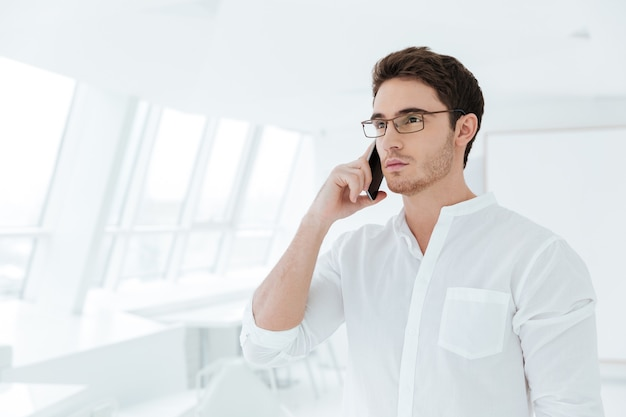 Photo of serious young man dressed in white shirt standing near big white window while talking by phone. look aside.