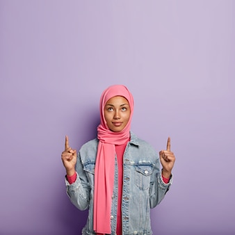 Photo of serious young muslim woman points upwards with both fore fingers, wears pink scarf, wears pink and denim jacket, isolated over purple wall. people, advertisement and promotion.
