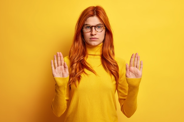 Photo of serious young redhead woman shows stop gesture makes forbidden sign pulls palms towards, wears optical glasses and turtleneck.