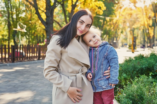 Photo session of mother with daughter in autumn park