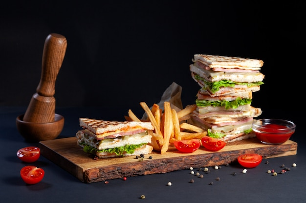 Photo session new menu of coffee house, fresh club sandwich with chicken and vegetables, lettuce salad, french fries and ketchup on wood