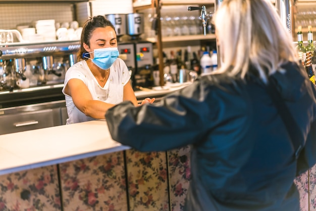 Photo session with a waitress with a face mask in a bar. delivering a coffee to a client