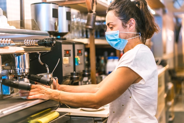 Photo session with a waitress with a face mask in a bar. heating water in the machine to put a tea