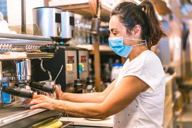 Photo session with a waitress with a face mask in a bar. heating water in the machine