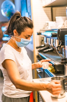 Photo session with a waitress with a face mask in a bar. preparing a coffee cut