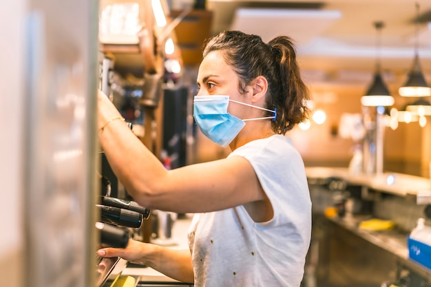 Photo session with a waitress with a face mask in a bar. preparing coffees in the machine