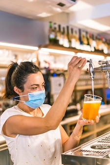 Photo session with a waitress with a face mask in a bar. putting a cold beer