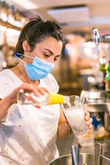 Photo session with a waitress with a face mask in a bar. putting a gin and tonic in a glass