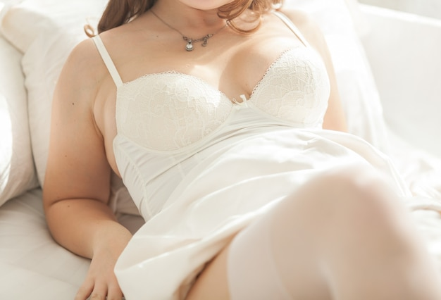 Photo of sexy female breast in corset at bed