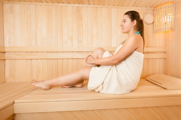 Photo of sexy woman in towel relaxing at steam bath